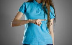 La fille dans le T-shirt bleu dirigeant le doigt du côté droit indique Photos stock
