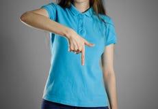 La fille dans le T-shirt bleu dirigeant le doigt sur le bas indique Photographie stock