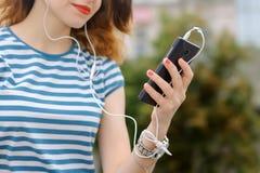La fille dans le T-shirt rayé écoute la musique photo libre de droits