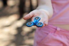 La fille dans le T-shirt rose joue le fileur bleu en métal dans des mains sur la rue, femme jouant avec un jouet populaire de fil Photos stock