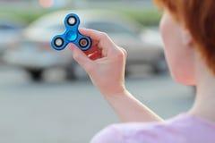 La fille dans le T-shirt rose joue le fileur bleu en métal dans des mains sur la rue, femme jouant avec un jouet populaire de fil Image stock