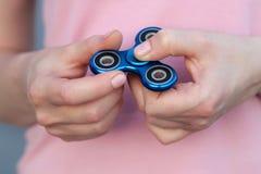 La fille dans le T-shirt rose joue le fileur bleu en métal dans des mains sur la rue, femme jouant avec un jouet populaire de fil Images stock