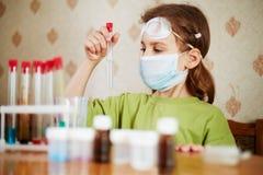La fille dans le respirateur regarde attentivement le tube à essai images stock