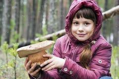La fille dans les bois avec un champignon blanc Photo stock
