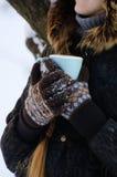 La fille dans les gants a étreint sa tasse de thé, fond neigeux blanc, visage n'est pas évidente Photos stock