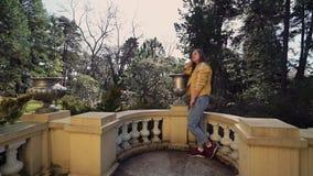 La fille dans les jeans et des espadrilles se tient sur un balcon antique et admire la beauté autour dans les sunlights banque de vidéos