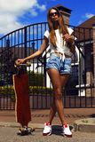 La fille dans les shorts blancs de gilet et de jeans pose avec photographie stock libre de droits