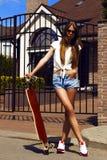 La fille dans les shorts blancs de gilet et de jeans pose avec Photographie stock
