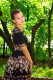 La fille dans la robe bariolée noire marche le long du vieux parc Photos libres de droits
