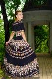 La fille dans la robe bariolée noire marche le long du vieux parc Image libre de droits