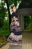 La fille dans la robe bariolée noire marche le long du vieux parc Photographie stock libre de droits
