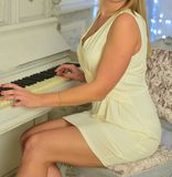 La fille dans la robe blanche s'assied derrière le piano blanc Belle femme dans la robe blanche au piano Fille sexy dans une sall photographie stock