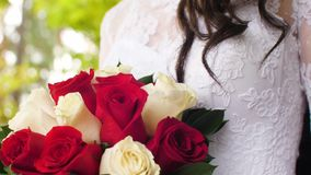 La fille dans la robe blanche tient le bouquet des roses rouges et blanches Plan rapproché banque de vidéos