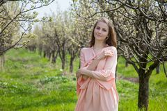 La fille dans la robe de pêche marche par un jardin de floraison Image libre de droits