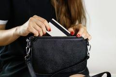 La fille dans la robe noire retire la carte de crédit d'une bourse noire Cl photos libres de droits
