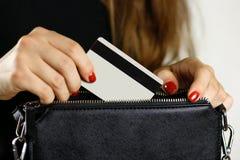 La fille dans la robe noire retire la carte de crédit d'une bourse noire Cl images libres de droits