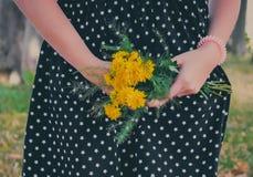 La fille dans la robe noire tient les fleurs jaunes Photographie stock