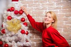 La fille dans la robe rouge décorent l'arbre de Noël avec des ornements Noël de attente Choses que vous devez faire avant des vac photographie stock