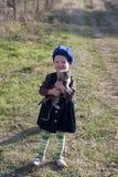 La fille dans un béret sourit avec un chaton sur ses mains Photos stock