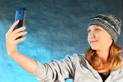 La fille dans un chapeau tricoté avec les cheveux rouges fait un selfie sur un smartphone sur un fond bleu dans le studio photo libre de droits