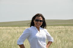 La fille dans un chemisier blanc et les lunettes de soleil en été mettent en place Image libre de droits