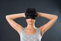 La fille dans un gilet léger avec les yeux a attaché près Photographie stock libre de droits