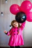 La fille dans un imperméable rose photographie stock