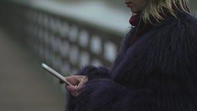 La fille dans un manteau de fourrure met dessus des écouteurs clips vidéos