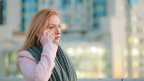 La fille dans un manteau rose avec le téléphone marche sur une ville moderne fond des gratte-ciel banque de vidéos