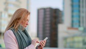 La fille dans un manteau rose avec le téléphone marche sur une ville moderne fond des gratte-ciel clips vidéos