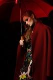 La fille dans un manteau rouge avec un parapluie rouge sous la pluie Images stock