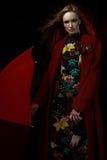 La fille dans un manteau rouge avec un parapluie rouge sous la pluie Photographie stock