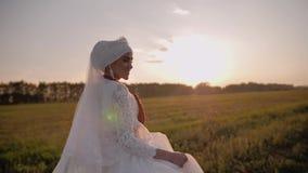 La fille dans une belle robe nationale blanche est un beau pré dans le soleil égalisant Belle jeune fille clips vidéos
