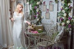 La fille dans une belle robe parmi les fleurs Photographie stock libre de droits