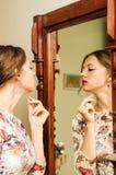 La fille dans une belle robe regarde dans le miroir Photos stock