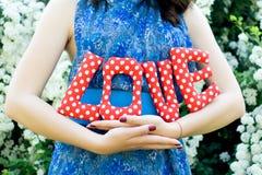 La fille dans une robe bleue tenant des lettres d'un tissu de textile Photographie stock libre de droits
