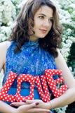 La fille dans une robe bleue tenant des lettres d'un tissu de textile Photo stock