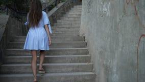 La fille dans une robe légère monte les escaliers clips vidéos