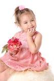 La fille dans une robe rose avec la fleur pense Image libre de droits