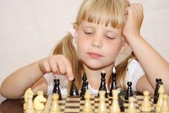 La fille dans une robe rose joue à des échecs Photos libres de droits