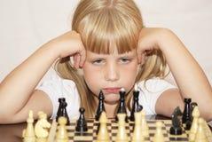 La fille dans une robe rose joue à des échecs Photos stock