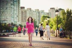 La fille dans une robe rose marche autour de la ville photographie stock libre de droits