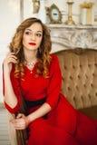 La fille dans une robe rouge avec la bijouterie fantaisie d'or Image libre de droits
