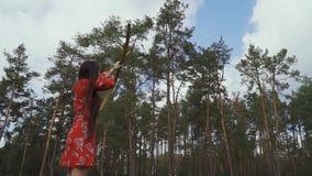 La fille dans une robe rouge a lancé une flèche dans le ciel banque de vidéos