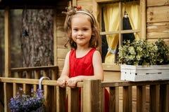 La fille dans une robe rouge pose dans une cabane dans un arbre Image libre de droits
