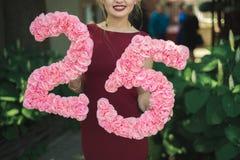 La fille dans une robe rouge tient un chiffre de 25 Photographie stock