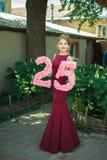 La fille dans une robe rouge tient un chiffre de 25 Image stock