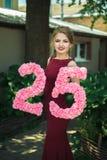La fille dans une robe rouge tient un chiffre de 25 Photographie stock libre de droits