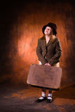La fille dans une veste tient un sac lourd Photographie stock