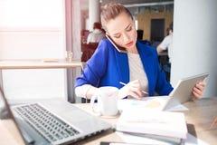 La fille dans la veste bleue s'assied à la table et au travail Elle parle au téléphone et note l'information aussi photographie stock libre de droits